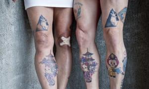 the Hello Kitty-tattooed legs of two women fans