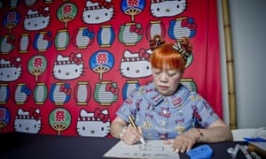 Official illustrator Yuko Yamaguchi sits and draws, an array of Hello Kitty designs behind her