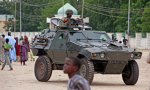 A Nigerian soldier patrols in an armored car in Maiduguri