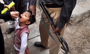 A policeman escorts a Pakistani health worker as she administers the polio vaccine in Karachi