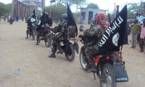 Uniformed Al-Shabaab men ride through town on motorbikes and pickup trucks.
