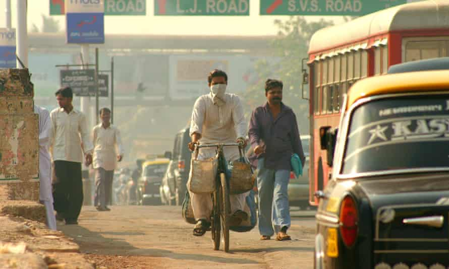 Commuters masked against air pollution negotiating city traffic in Mumbai.