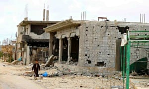 A boy walks next to the ruins of buildings near Benghazi