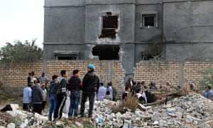 Libyan citizens stand beside a building damaged in the national army's air strikes in Tripoli.