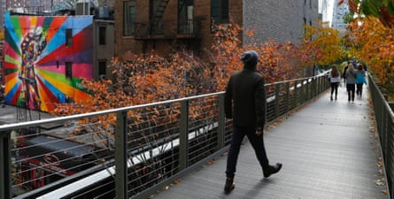 People walk along High Line park on a warm autumn day in New York