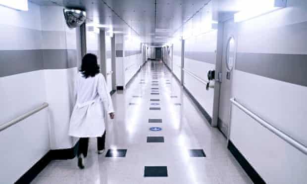 A clinician walks down a hospital corridor