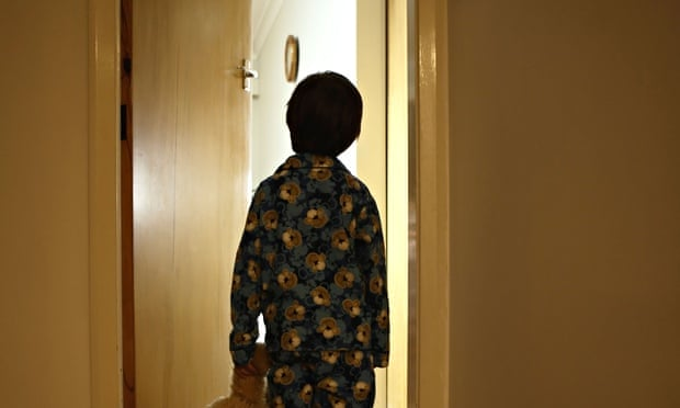 Six year old boy stands in corridor in pyjamas with teddy bear