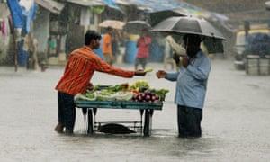 A man buys vegetables on a flooded Mumbai street