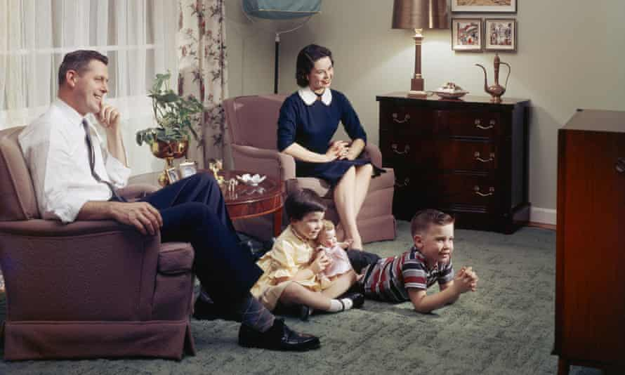A young family watching television together in their lounge, 1957