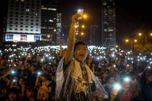 Protesters sing songs and wave their cell phones in the air after a massive thunderstorm passed over outside the Hong Kong Government Complex on September 30, 2014 in Hong Kong, Hong Kong. Thousands of pro democracy supporters continue to occupy the streets surrounding Hong Kong's Financial district.