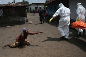 A woman throws a handful of soil towards the body of her sister as Ebola burial team members take her for cremation on 10 October in Monrovia, Liberia. The woman had died outside her home earlier in the morning while trying to walk to a treatment center, according to her relatives. The burial of loved ones is important in Liberian culture, making the removal of infected bodies for cremation all the more traumatic for surviving family members