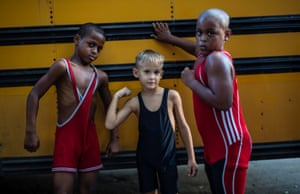 Young wrestlers Braimond Sanchez, from left, Raimel Lazaro and Junior Lazaro strike a pose for a photo, during a training session in a park in Old Havana, Cuba. About 20 children are learning to wrestle under the watchful eye of former wrestler Michael Guerra