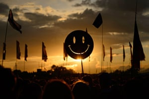 A smiley face sign is carried through the crowds as the sun sets on the first day of the Glastonbury Festival of Music and Performing Arts in Somerset