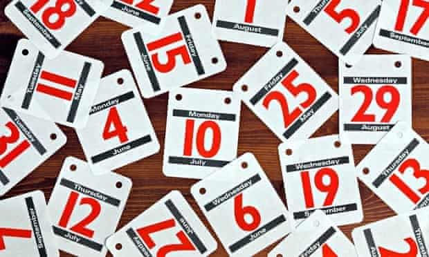 Photo of various calendar dates spread out on a wooden desk.