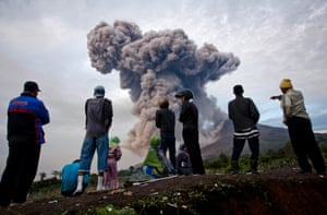 Watching as Mount Sinabung spews pyroclastic smoke, 8 January 8 in Karo District, North Sumatra, Indonesia. The number of displaced people has increased to 22,000 in Western Indonesia as Mount Sinabung continues to spew ash and smoke after several eruptions