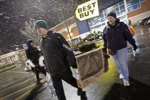 Alex and Lisa Hardman carry a TV from the Best Buy store in Dartmouth, Massachusetts, after waiting in line for the store to open at 1am