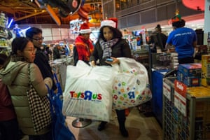 A woman carries her purchases from Toys R Us in Times Square
