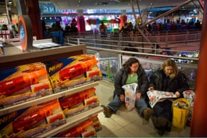 Women flip through a coupon book at Toys R Us in New York