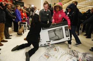 "Shoppers wrestle over a television as they compete to purchase retail items on ""Black Friday"" at an Asda superstore in Wembley, north London November 28, 2014."