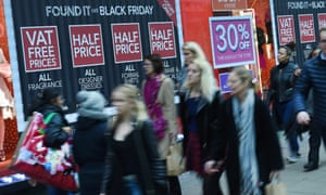Shoppers pass a store offering Black Friday sales on Oxford Street in London.