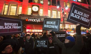 Protesters hold signs aloft outside Macy's before the kick off of Black Friday sales in New York