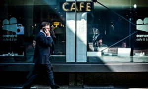 Man on mobile phone walks past cafe