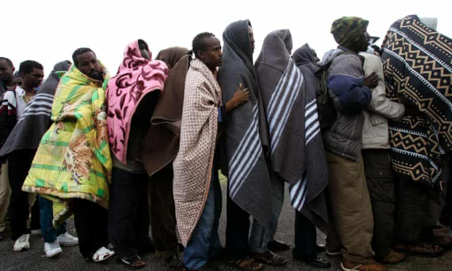 Somali and other refugees stand in line for food at a makeshift camp near the small town of Scarborough, South Africa.