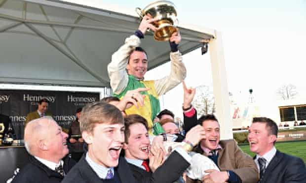 Leighton Aspell holding the Hennessy Gold Cup after his triumph aboard Many Clouds at Newbury