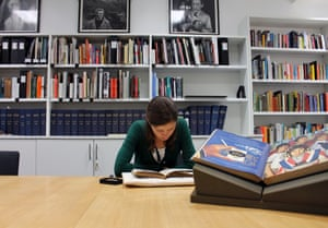 R is for Reading Room. The GNM Archive reading room at Kings Place is open to staff members and external researchers by appointment. Readers can access paper records from the archives, reference books from the historical research library and electronic records stored in the digital repository. The image shows a researcher consulting material in the reading room against a backdrop of books from the historical research library.