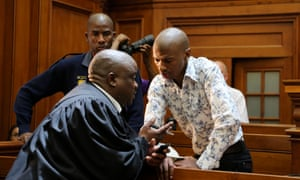 Xolile Mngeni leans over a bench in court to speak with his lawyer, at his trial for the murder of Anni Dewani