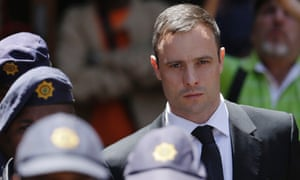 Oscar Pistorius, accompanied by police officers, leaves the high court in Pretoria.
