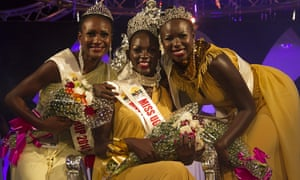 Three finalists of the Miss Uganda pageant pose for a photograph. The winner, Leah Kalanguka, sits in the middle.