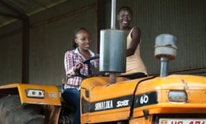 Two Ugandan women pose with a tractor as part of the contest for Miss Uganda, now being used to promote agricultural values.