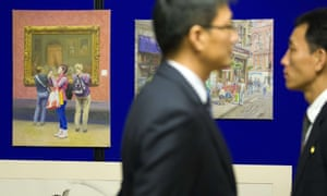 Staff at the North Korean embassy in west London supervise the exhibition on 3 November 2014.