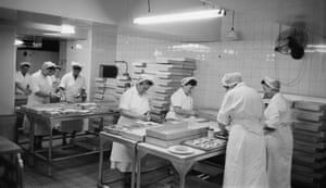 Workers prepare sandwiches in the kitchen of a store