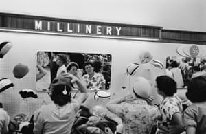 Shoppers try on hats in the millinery department. All Photographs: Getty Images