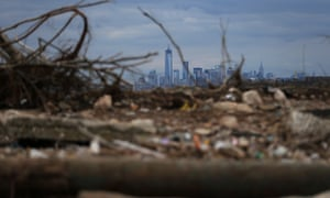 Debris sits on a still-closed Staten Island beach area damaged by flooding from hurricane Sandy, with Lower Manhattan and One World Trade Center in the background.