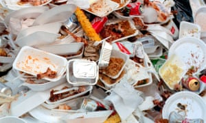 A pile of fast food wrappers, trays, and packetsdiscarded food waste