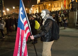 million mask protester with a flag saying you cant bomb your way to a better world