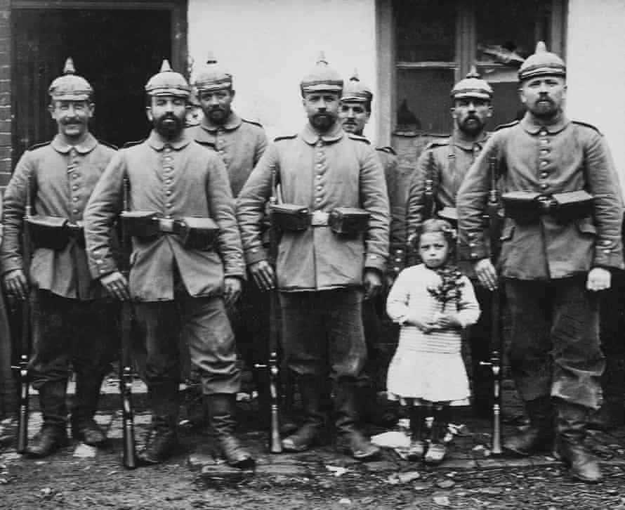 A little girl clutches a small Christmas tree while standing with a German military outfit early in WWI somewhere in war torn France.