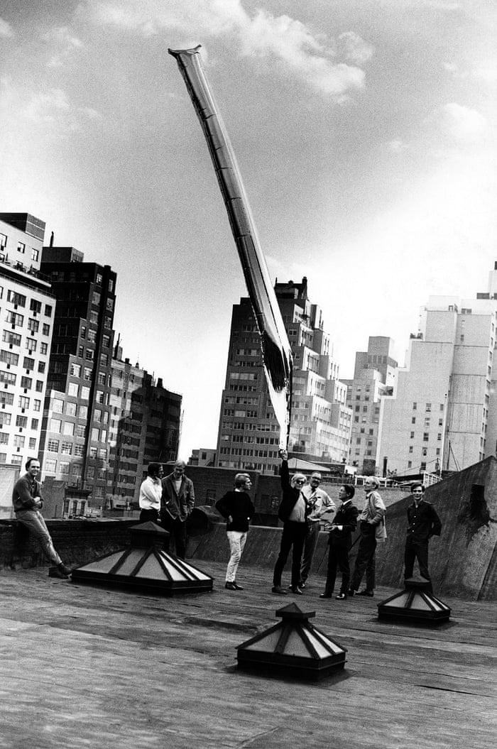 Andy Warhol with silver balloon sculpture, the factory 'Andy, Gerard Malanga and onlookers release the silver 'cloud' from the Factory rooftop on 47th Street. Factory regulars would occasionally sneak up there to smoke cannabis but on this day Andy released a floating work of art to the sky.'