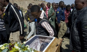 A man pays his respects to a killed mine worker as his coffin is carried away.