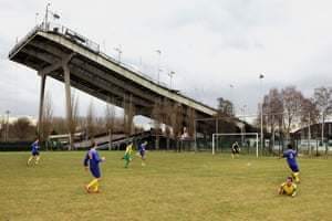 """Photos from the exhibition """"Crossing the Field: WWI, Football & the Christmas Truce"""". Belgian photographer Jurgen Vantomme's images of football matches taking place across Belgium show the sport watched by a handful of people set against austere backdrops of industrial plants or power station chimneys.. KFCStabelino, 2014"""