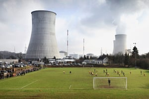"""Photos from the exhibition """"Crossing the Field: WWI, Football & the Christmas Truce"""". Belgian photographer Jurgen Vantomme's images of football matches across Belgium show the sport watched by a handful of people set against backdrops of industrial plants. RFC Huy youth team playing in the shadow of the Tihange nuclear plant."""