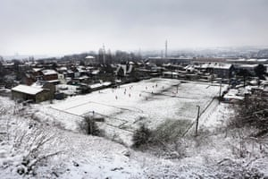 """Photos from the exhibition """"Crossing the Field: WWI, Football & the Christmas Truce"""". Belgian photographer Jurgen Vantomme's images of football matches taking place across Belgium show the sport watched by a handful of people set against austere backdrops of industrial plants or power station chimneys. A.S. Chatelineau FC."""