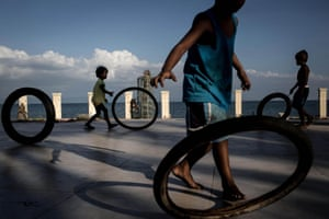 """Chris McGrath too was in Leyte, returning to the devastating scenes that he photographed a year ago. Here, children play with bike tyres in a destroyed resort building on the coastline at San Jose. <a href=""""http://www.theguardian.com/world/ng-interactive/2014/nov/07/typhoon-haiyan-tacloban-one-year-on-interactive"""">To see more images by Chris McGrath from the aftermath of the typhoon and the same scene today click here</a>"""