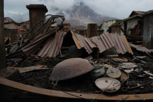 Houses damaged from the eruption of the mount Sinabung volcano in Sumatra, Indonesia, lie in ruins at the abandoned village of Sukameriah. More than 33,000 residents have been forced to flee their homes since an eruption in February