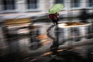 A person shelters from the elements in Lyon, France, where 6,500 homes were left without power after heavy rains and strong winds
