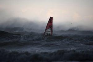 A windsurfer rides in the Tyrrhenian sea near Aurelia on the northern coast of Italy