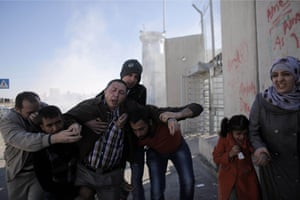 Palestinians flee tear gas fired by Israeli border police during clashes at a checkpoint between Shuafat refugee camp and Jerusalem